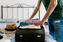 Young Hispanic Man Unpacking His Suitcase In An Apartment. Travel And Vacation Concept