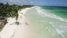 Aerial Reversing Over Idyllic Caribbean Beachside Community, With Bright Sunlight, Vast Green Landscape, Gleaming Sand, And Crashing Waves - Tulum, Mexico