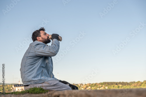Young sick desperate depressed alcoholic homeless man sitting on the dockyard dr Fototapet