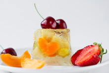 Jelly Dessert With Tangerine Slices And Grapes On A White Plate Is Decorated With Fresh Pieces Of Strawberries, Apricots And Cherries On A White Background. Close-up. Space For Text