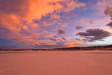 Winter Sunset - Colorful Clouds Rolling Over A Frozen Mountain Lake On A Cold And Windy Winter Evening. Chatfield State Park, Denver-Littleton, Colorado, USA.