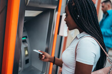 Cheerful African American Woman Using Credit Card And Withdrawing Cash At The ATM