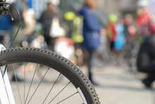 A Close Up Of A Bicycle Wheel On The Blurry Background Of The City Crowd. Text Space.