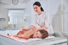 Focused Female Masseur Doing A Deep Tissue Massage Therapy In Spa Senter