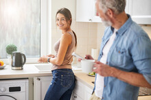 Happy Cheerful Female Looking To Her Husband In The Kitchen