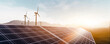 solar panels and wind power turbines in a sunset