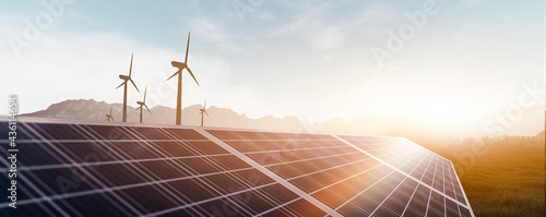 Fotografiet solar panels and wind power turbines in a sunset