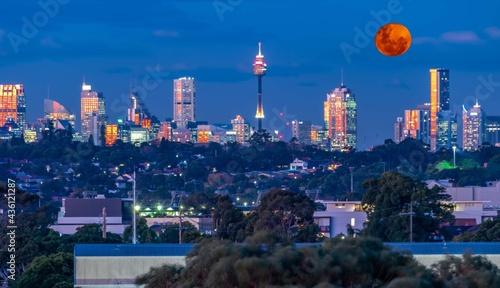 Fotografia Large orange moon rising behind Sydney CBD buildings NSW Australia