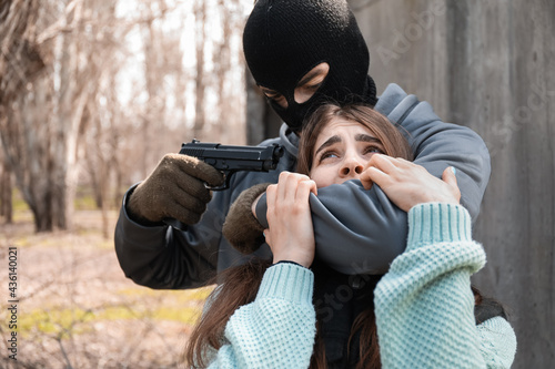 Foto Terrorist aiming at female hostage outdoors