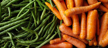 A Pile Of Fresh Raw Carrots On One Side And Green Beans On Other Side