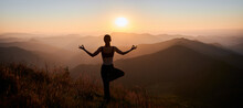 Back View Of Woman Practicing Yoga On Background Of Evening Mountains. Meditating Female Is Balancing On One Leg After Sunset. Panorama.