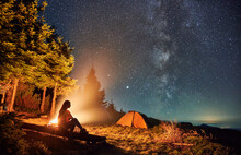 Young Woman Hiker Sitting On Bench Near Bonfire Under Magical Sky With Stars And Milky Way. Beautiful View Of Night Starry Sky Over Grassy Hill With Camp Tents And Girl Traveler Near Campfire.