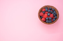 High Angle Of Fresh Raspberries And Blueberries In A Basket Isolated On Pink Background