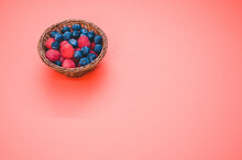 High Angle Shot Of Fresh Raspberries And Blueberries In A Basket Isolated On Red Background