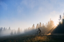 Side View Of Young Man In Cycling Suit Riding Bicycle Illuminated By Morning Sunlight. Male Bicyclist Cycling On Grassy Hill In The Morning. Concept Of Sport, Bicycling And Active Leisure.