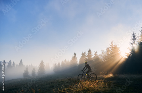 Fotografija Side view of young man in cycling suit riding bicycle illuminated by morning sunlight
