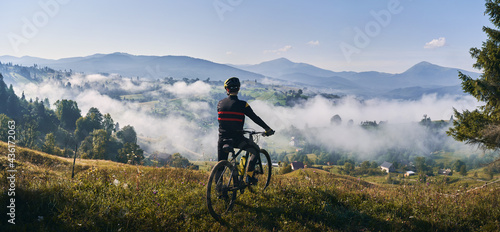 Slika na platnu Man riding bicycle on grassy hill and looking at beautiful misty mountains