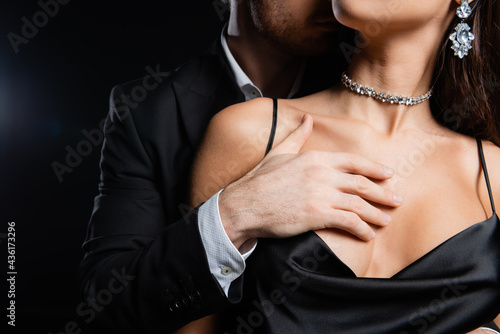 Fototapeta cropped view of man in black blazer and white shirt holding hand on breast of wo