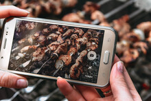 A Person Takes A Picture Of A Barbecue On His Phone
