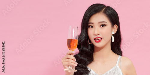 Fotografiet Beautiful asian girl in evening dress smiling and holding glass of champagne