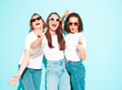 Leinwandbild Motiv Three young beautiful smiling hipster female in trendy same summer white t-shirt and jeans clothes. Sexy carefree women posing near light blue wall in studio. Cheerful and positive models having fun