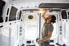 Man Attaching Thermal Insulation In A Camper Van