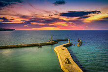 The Harbour And Lighthouses At Sunset In Whitby Abbey, North Yorkshire, UK