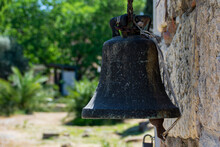 An Old Brass Bell Hanging On A Wall Of A House.