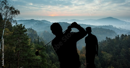 Canvas Composition of silhouette of golf players over landscape, clouds on blue sky wit