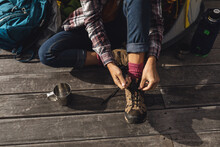 Low Section Of Caucasian Woman Camping, Sitting Outside Tent On Deck Putting On Boots