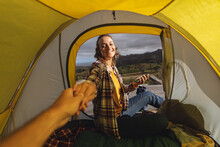 Smiling Caucasian Woman Camping, Sitting Outside On Mountainside Deck Holding Hand Of Friend In Tent