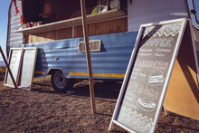 General View Of Food Truck And Menu Board By Seaside On Sunny Day
