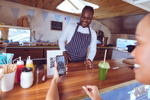Smiling African American Man In Food Truck With Female Customer Reading Qr Code With Smartphone
