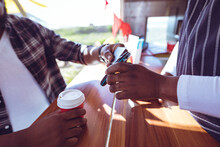 Midsection Of African American Man In Food Truck Taking Smartphone Payment Holding Terminal