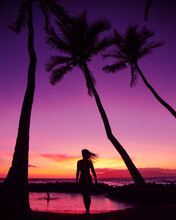 Woman Walking Towards The Purple And Pink Sunset