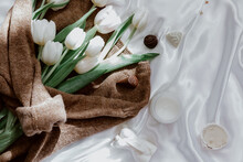 Bunch Of White Tulips Wrapped In A Woolly Sweater On A Silk Tablecloth With Candles