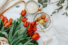 Cup Of Coffee And Plate Of Macaroons Next To A Bunch Of Tulips