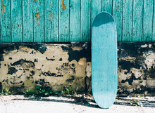 Green Wooden Skateboard On Deteriorated Wall On A Sunny Day. Skateboarding Background, Street Extreme Sport.