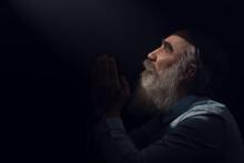 A Senior Man Standing In Dark Smoky Background Light Ray From Above. Prayer Gesture