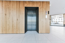 Entrance Lobby Of Luxury Apartment Building With Wooden Wall Panels And Elevator Against Panoramic Windows