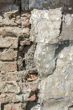 A Ruined Brick Wall With Remnants Of Plaster As A Natural Backdrop.