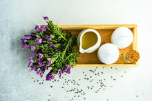 Overhead View Of Fresh Lavender Flowers On A Tray Next To A Jug With Oil And Two Block Candles