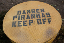 Manhole Cover With A Sign On It Saying 'danger Piranhas Keep Off'