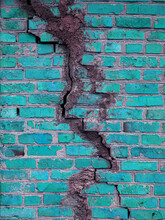 Texture Of A Brick Wall With Cracks In Turquoise Color. The Destroyed Ancient Wall Is Turquoise. Brick Background Copy Space.