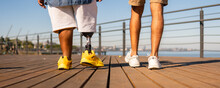 Black Man With Prosthetic Leg With Friend Walking In Deck Outdoors.