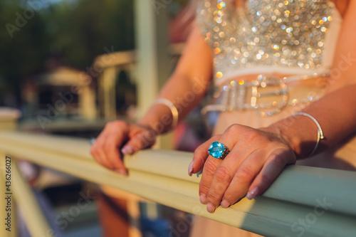 Tela woman's hands with green bracelets grabbing a railing.