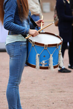 Girl Drummer With A Big Blue Drum Stands On The Street And Prepares To Perform At The Parade.