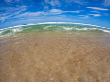 Extreme Wide Angle Beach Shot Of Incoming Surf With Clear Turquoise Water And Bright Blue Sky With Wispy Cirrus Clouds Overhead.