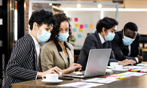 Fotografering Multiracial smart formal businesspeople sitting face to face meeting and making group discussion at office, wearing face masks as new normal to protect or prevent virus in outbreak pandemic crisis