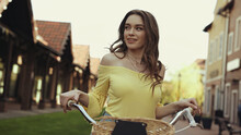 Happy Young Woman With Wavy Hair Riding Bike Outside.